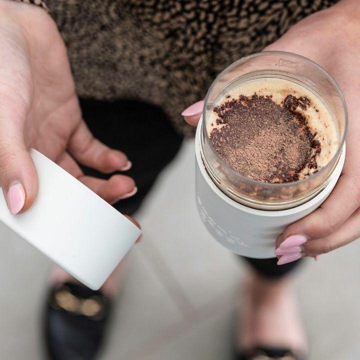 Frank Green Original cup fehér színű tritán utazó bögrében capuccinot tart egy női kéz.