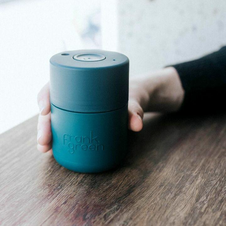 Frank Green original cup utazó bögre kézben tartva, fa asztalon.